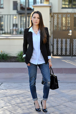 Hapa Time in a black blazer, blue shirt, distressed denim and heels