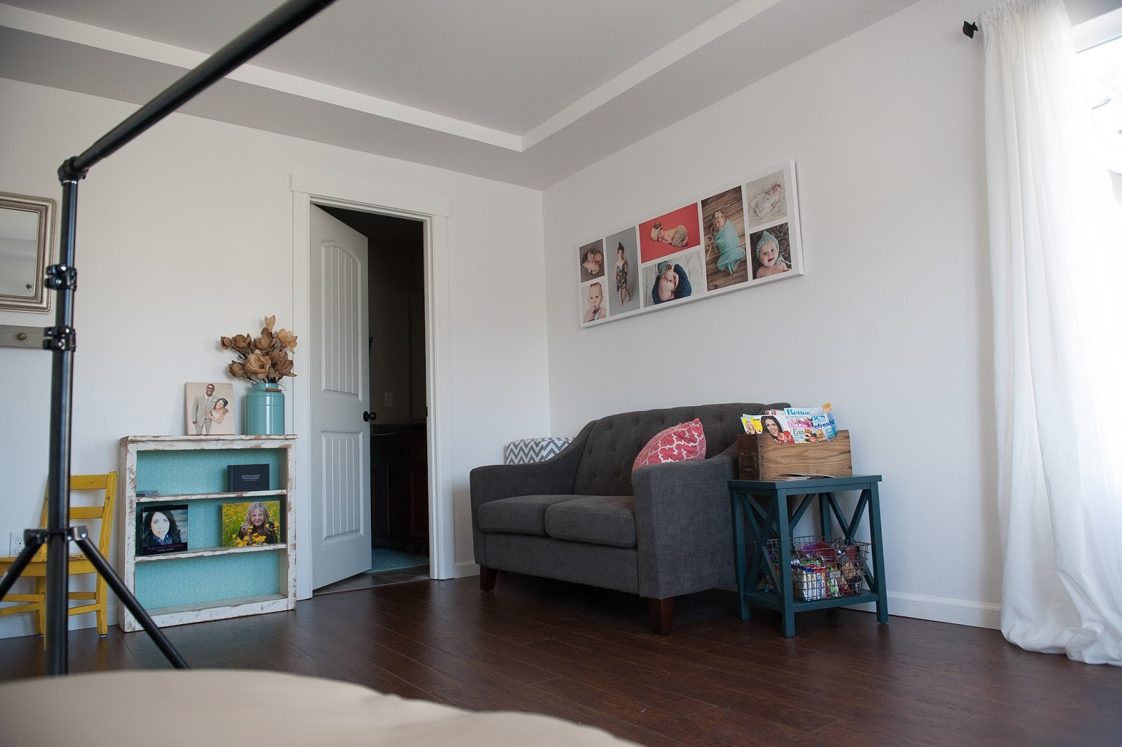 White Walls, Hardwood Floors, Gray Love Seat, and colorful accents