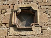 Detall de la finestra motllurada sobre el portal de l'església de Brics
