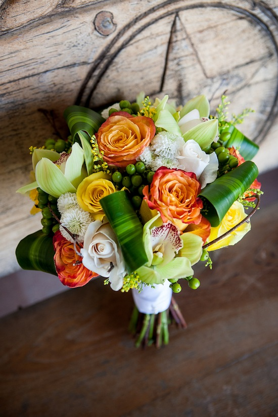 brides stunning bouquet with yellow and orange roses plus white poms and green buttons
