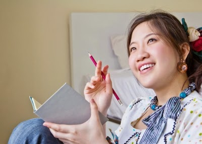 Asian lady poised to write in notebook