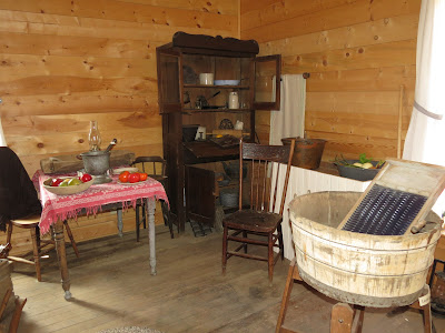 Interior view of replica settler's house at the Laura Ingalls Wilder Museum, showing washtub, table, and cabinet.