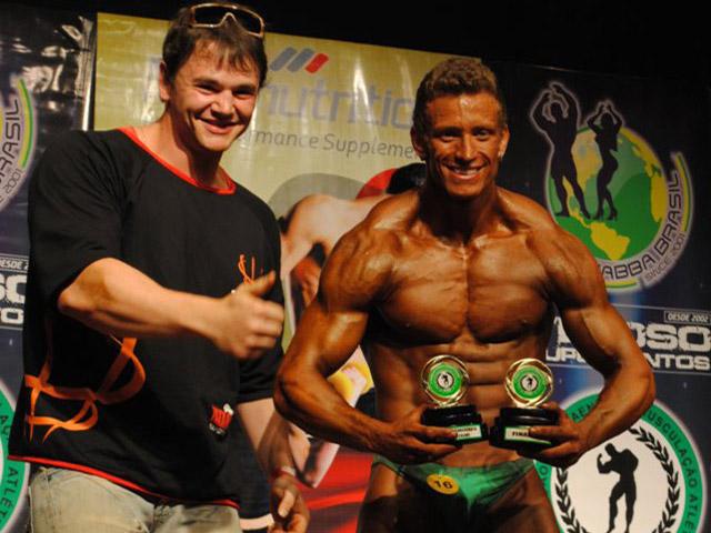 Filipe Marins posa para foto com os dois troféus ao lao do treinador Suel Nogueira