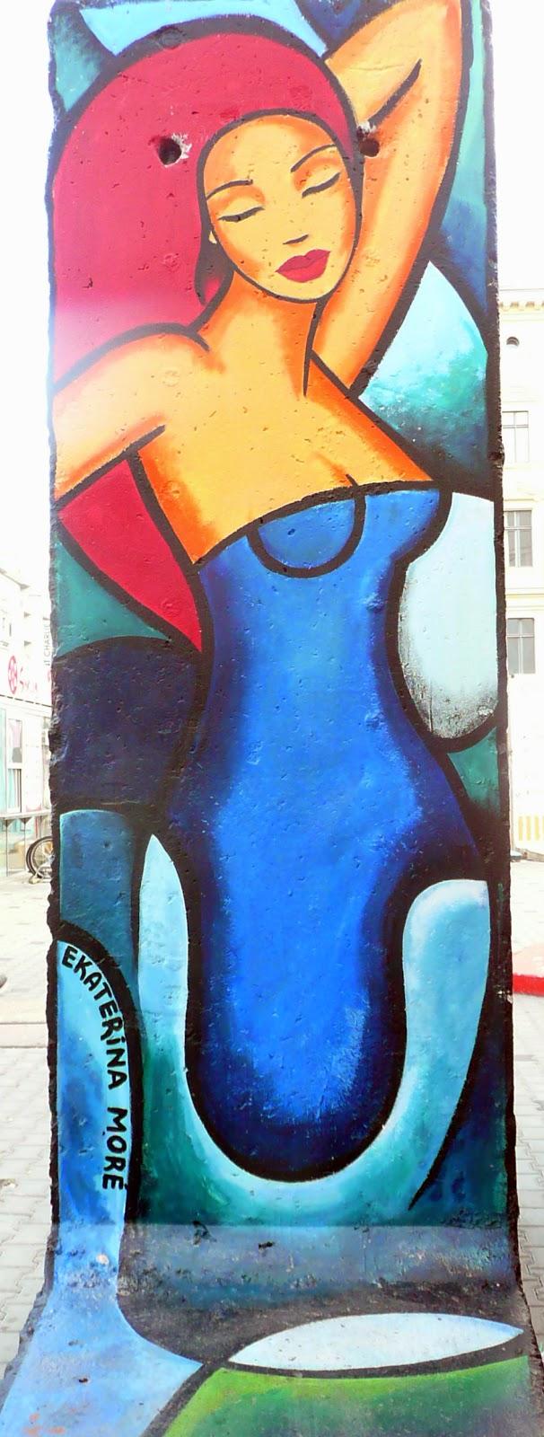 pieza de pop art representando una mujer pelirroja sobre resto del muro de Berlín