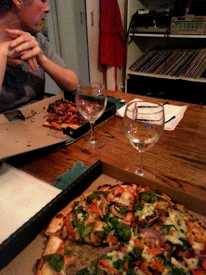 Dining table with pizzas and wine glasses on it.