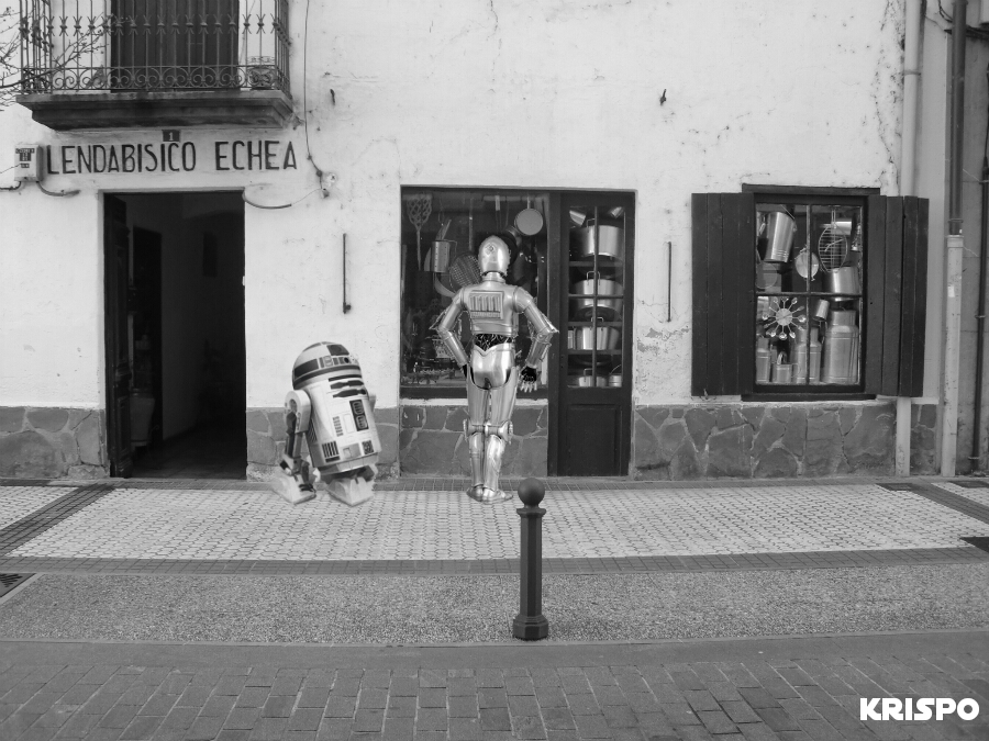 imagen en blanco y negro de los droids RD y C3PO en una calle de Hondarribia mirando escaparates