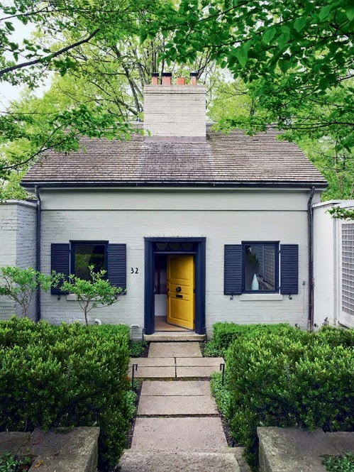white painted brick house yellow door