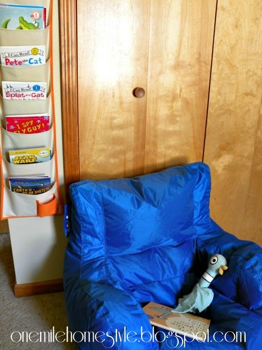 Kids room reading nook - hanging book organizer and blue chair