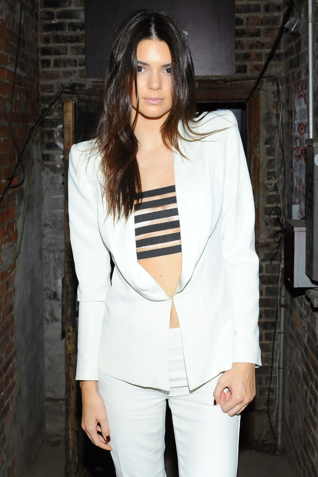Kendall Jenner wears a white pant suit with a bralet to the Interview Magazine September 2014 Issue Launch Party