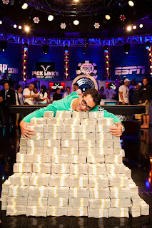 Esfandiari hugs his mountain of case (Joe Giron/WSOP)