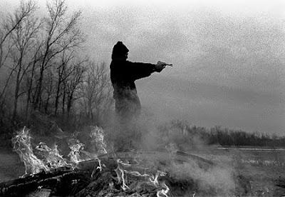 man shooting a handgun on a beach- black and white photo