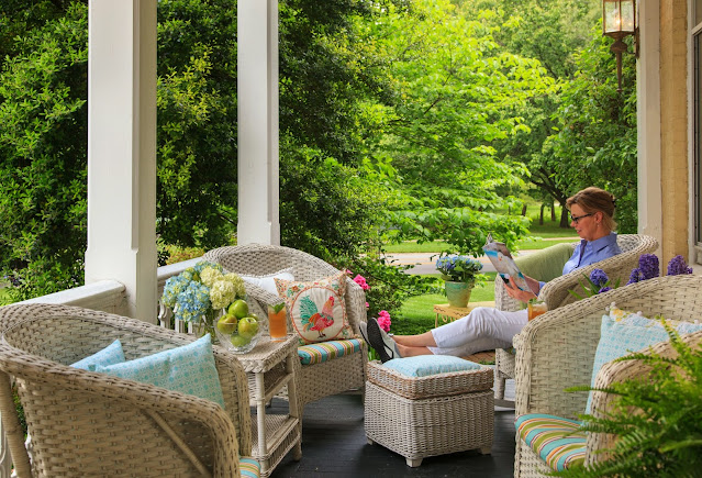 the front porch with four white wicker chairs with blue cushions and footstools and a guests sitting and reading in one chair with green trees in the background