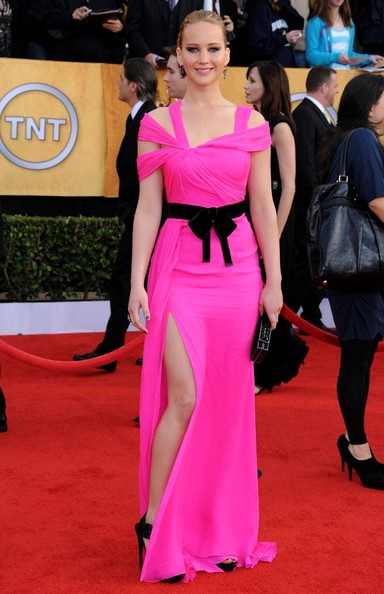 Jennifer Lawrence in a hot pink Oscar de la Renta gown with a thigh-high slit and cinched with a black velvet bow and paired with a black Judith Leiber box clutch, black Roger Vivier satin sandals and 18th century Fred Leighton rose-cut diamond pendant earrings at the 17th Annual Screen Actors Guild Awards held at The Shrine Auditorium on January 30, 2011 in Los Angeles, California.