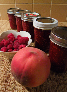 5 jars of jam with big peach and raspberries