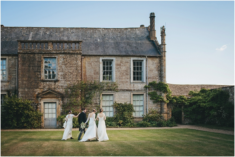 Three bridal models and the groom walking across the lawn