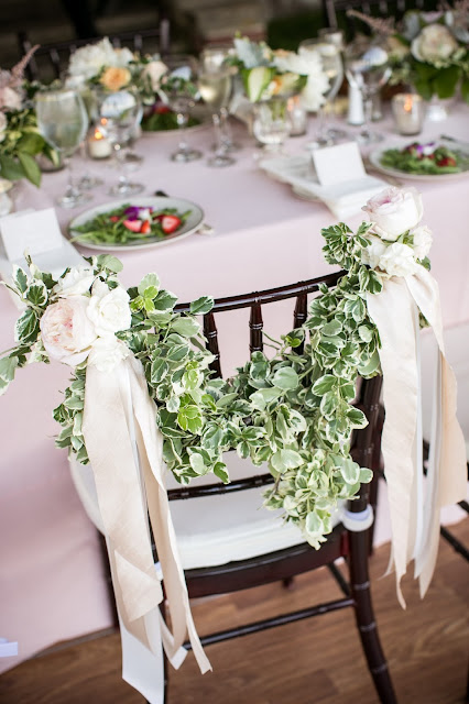 garland with roses bride and groom chairs