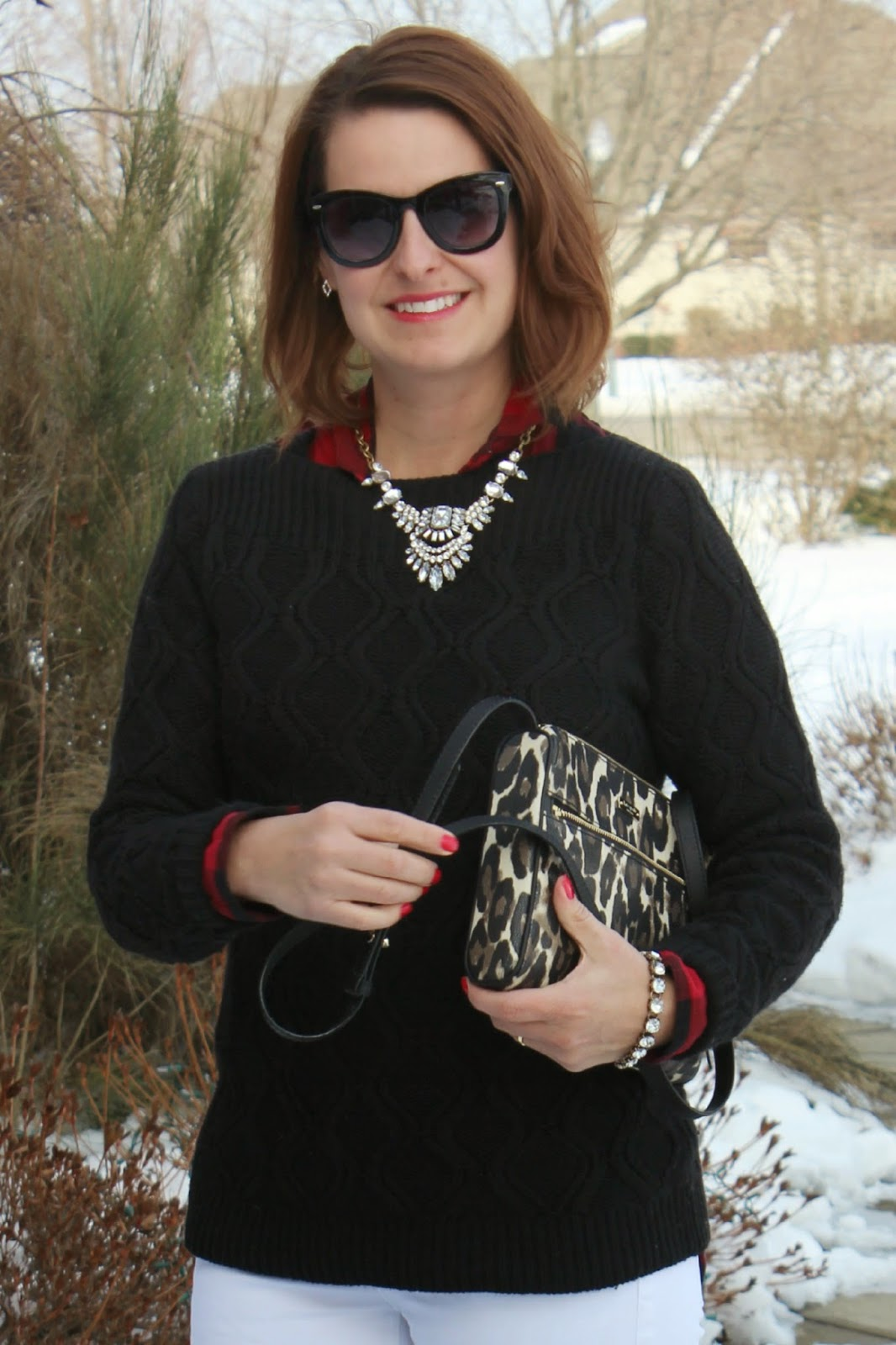 White jeans in winter, red and black buffalo plaid shirt, black sweater, crystal necklace, earrings, bracelet, black riding boots, Kate Spade leopard purse, winter look