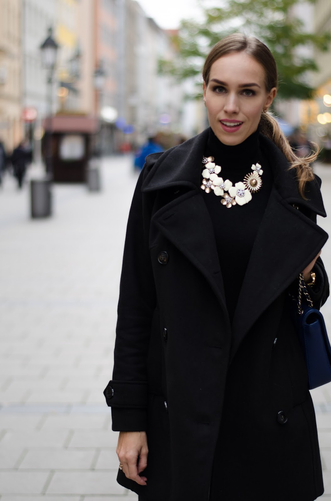 kristjaana mere black pea coat black turtlenect jumper gold white statement necklace
