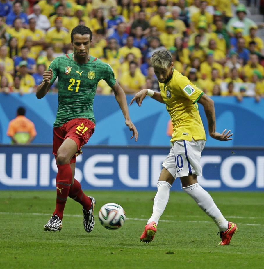 Brazil's Neymar kicks the ball past Cameroon's Joel Matip to score his side's first goal during the group A World Cup soccer match between Cameroon and Brazil at the Estadio Nacional in Brasilia, Brazil, Monday, June 23, 2014.