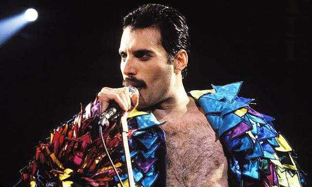 Na imagem: Freddie Mercury segurando o microfone e olhando para o horizonte, vestido de uma camisa espalhafatosa toda colorida e aberta deixando o peito exposto.