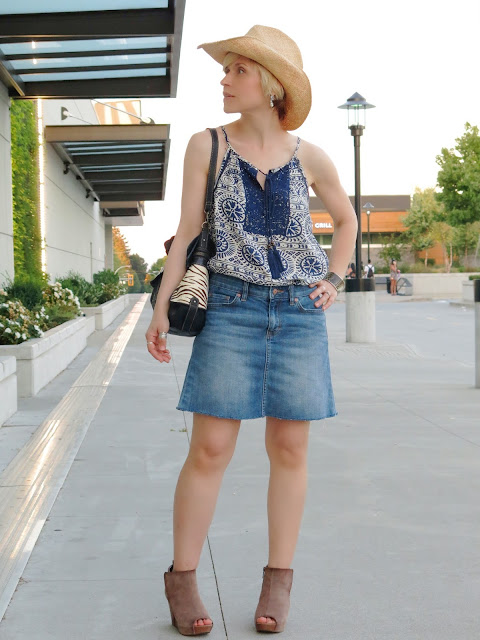 styling a peasant-style patterned camisole with a denim skirt, open-toe booties, and a cowboy hat