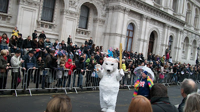 A polar bear costumed man carrying an Olympic Torch replica with the Olympic Rings on his chest.