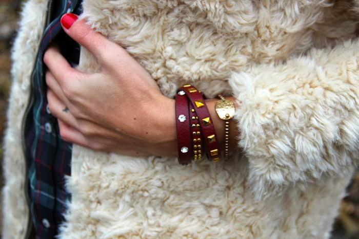 pulseras tachuelas doradas en cuero rojo, abrigo pelo, uñas rojas