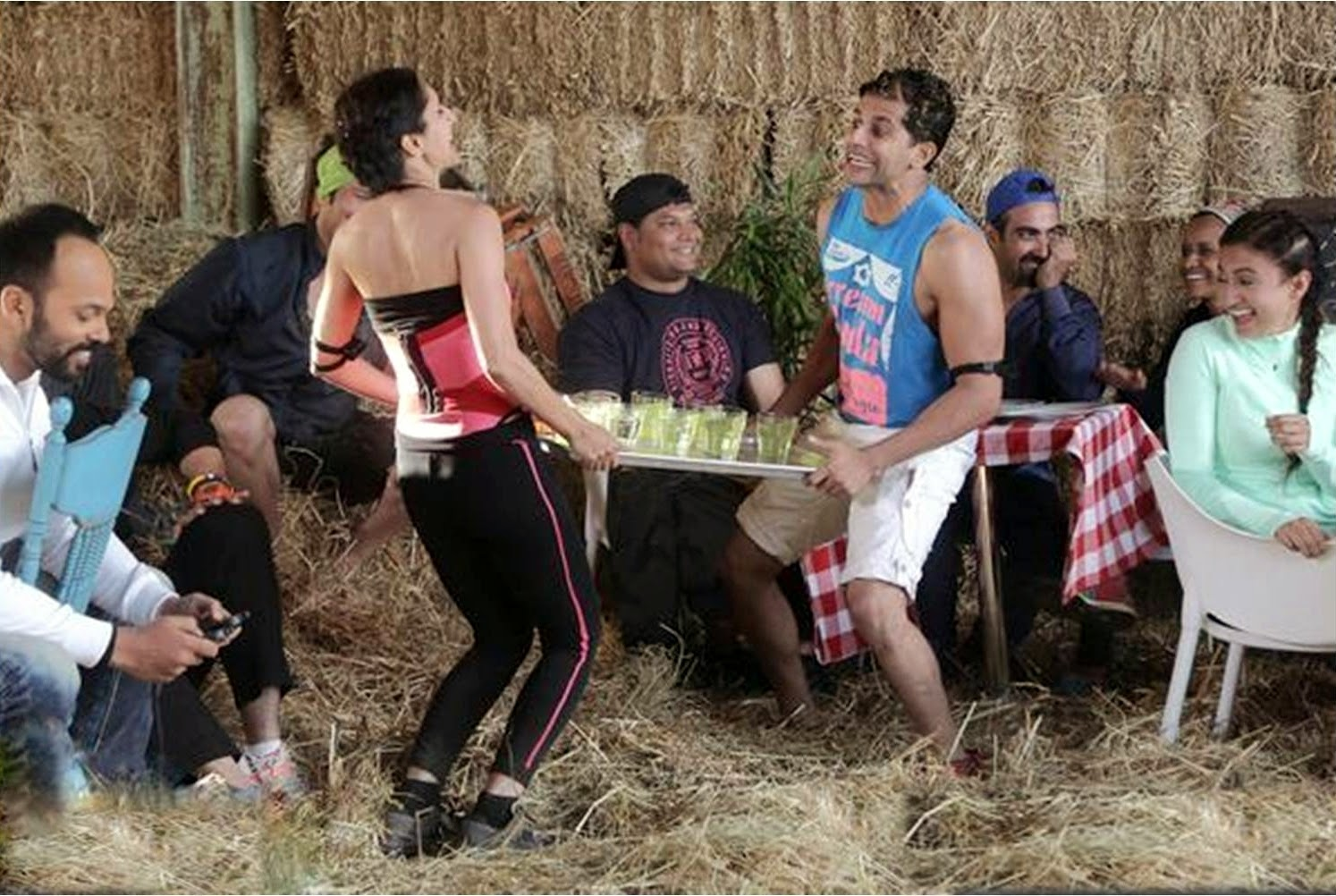 Khatron Ke Khiladi Karanvir and Teejay holding a trey while Rohit Shetty giving them mild electric shocks