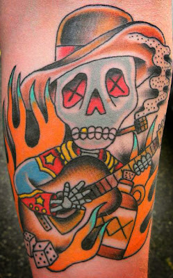 Tattoo of Country guitar playing skeleton with moonshine and corn cob pipe by Tattoo artist Mark Stewart for Triumph Tattoo
