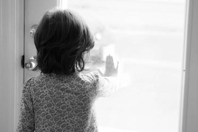 girl with hand on glass door