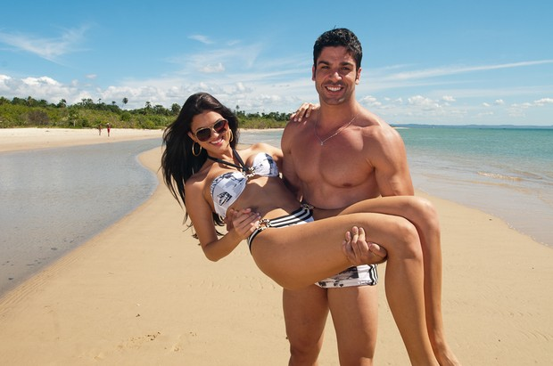 De sunga, Kadu Parga carrega modelo em ensaio para divulgar sua linha de moda praia