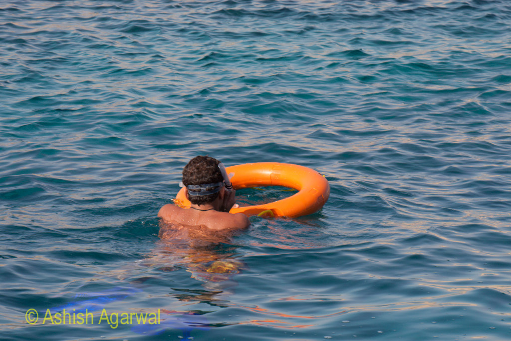 Man wearing snorkeling equipment clutching onto a rubber tube meant for floating