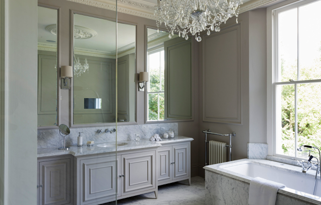 Grey master bathroom in a suburban London home with carved crown moulding, paneled walls, a crystal chandelier and marble bathtub