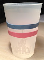 pink and blue silicone bands around a plastic Disney cup