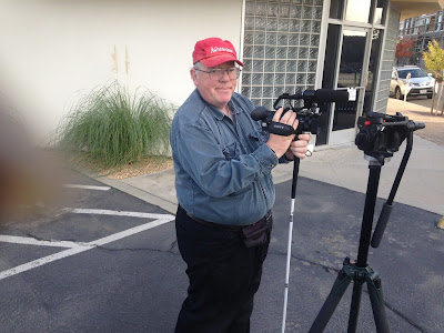William Elliott stands beside tripod on location shoot in downtown Fresno as part of the Field class at CMAC. Photo taken by Kevin Hobson