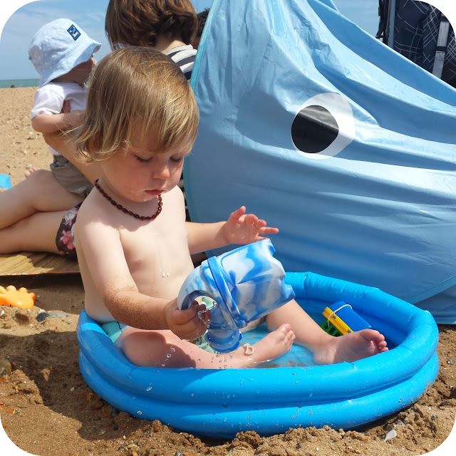 watering can in paddling pool, paddling pool at the beach