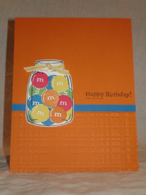 Orange birthday card with a stamped jar of M&Ms candy.