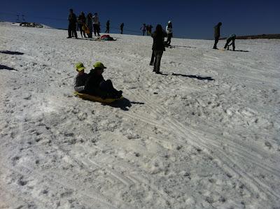 Dos de nuestros alumnos se tiran con un trineo por la nieve. Van los dos fuertemente agarrados al trineo para no caer.