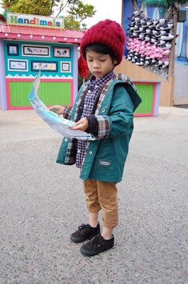 Niño perdido en el zoológico leyendo un mapa de ubicación