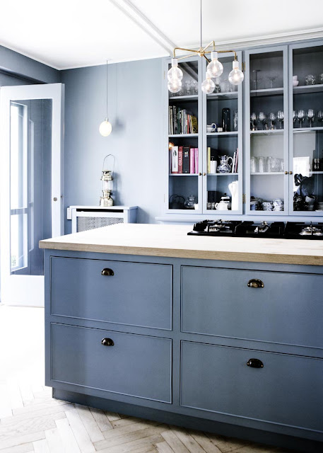 close up of blue cabinets in an entirely blue kitchen with herringbone wood floors