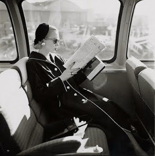 black and white image of woman reading on train