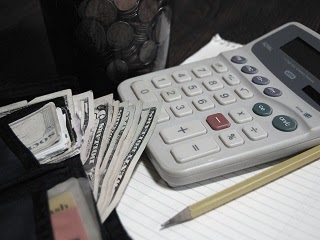 A wallet with money next to a calculator.