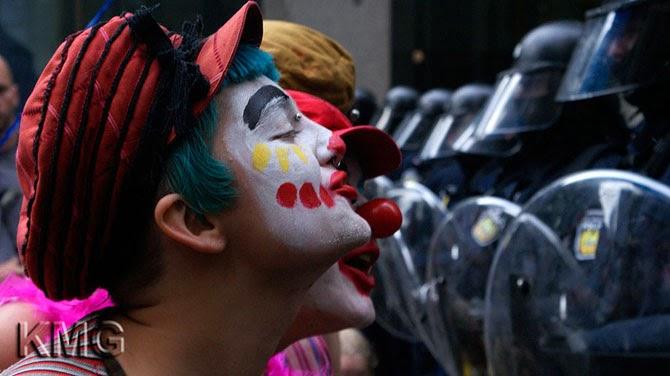 Демонстранты в костюмах клоунов развлекают полицейских во время встречи большой двадцатки в Торонто, Канада, 2010 год.