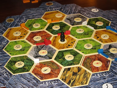 Settlers of Catan - The basic layout early in the game & my red territories are already being blighted by the robber