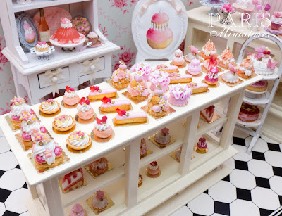 Individual pink pastries in 12th in a miniature pâtisserie setting