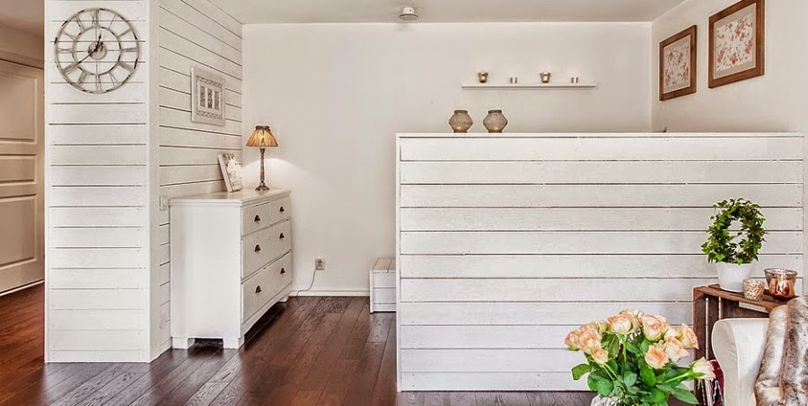 kawalerka, małe wnętrze, salon, sypialnia, białe wnętrze, kanapa, styl skandynawski, zegar, komoda, białe boazeria