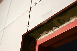 зафиксированная скотчем плитка над дверным проемом