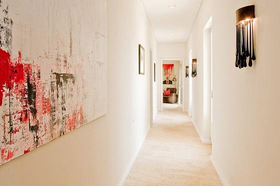 pasillo blanco con cuadros modernos y apliques vintage