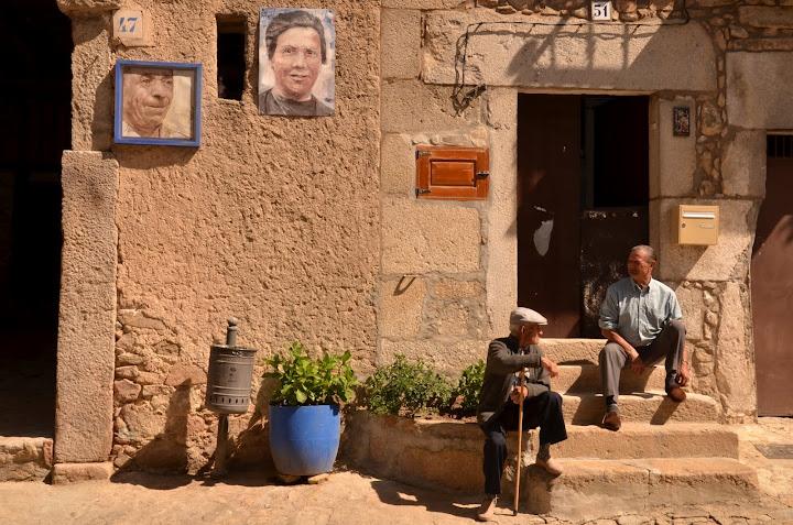 Una de las fachadas con retratos y dos vecinos e la localidad sentados al sol