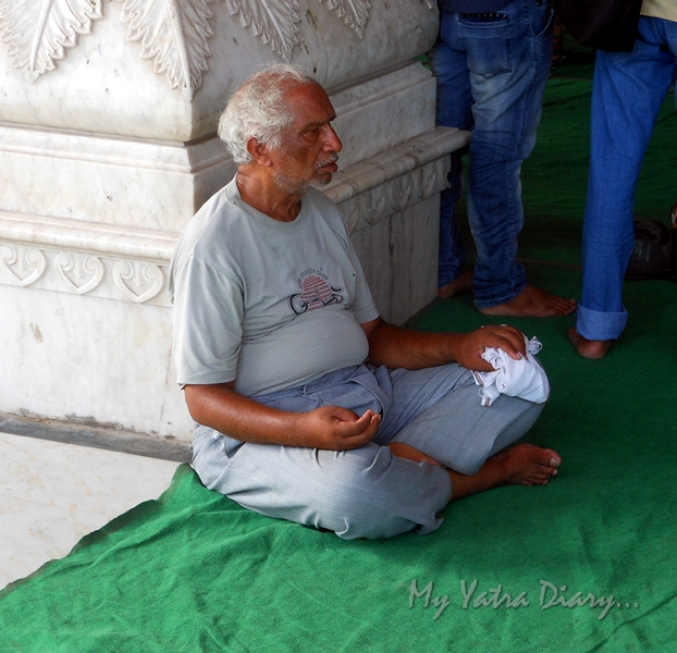 A devotee chanting prayers at the Govind Devji Temple, Jaipur, Rajasthan